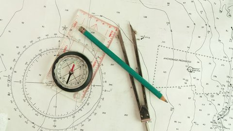 Male hands using compass & nautical charts to navigate, POV