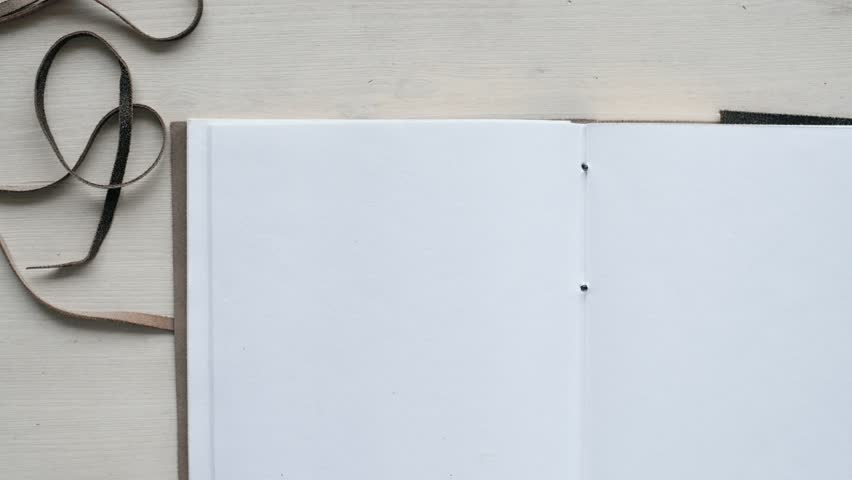 Man's hands open handmade diary book with white blank pages and leather cover, isolated on clean wooden table. Close up top view, mockup concept