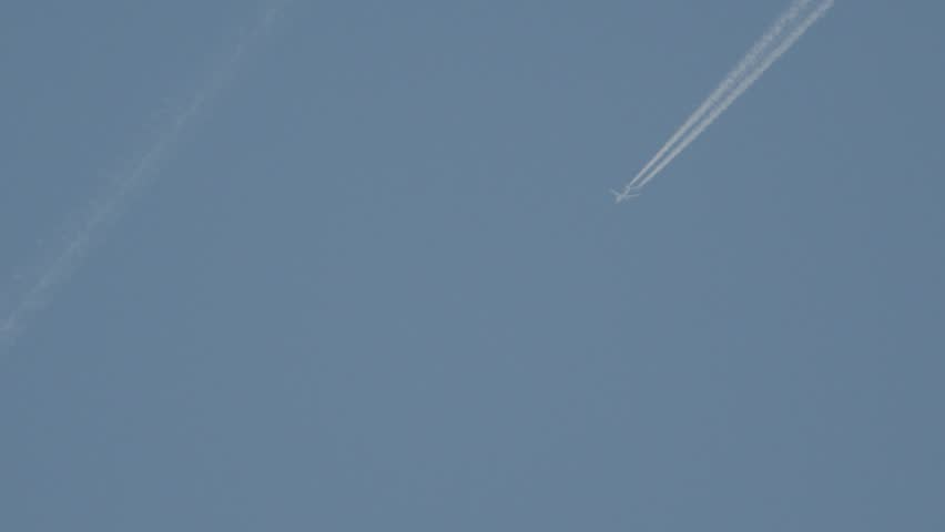 Jet airplane with trail against the blue sky, blurry image airplane.
