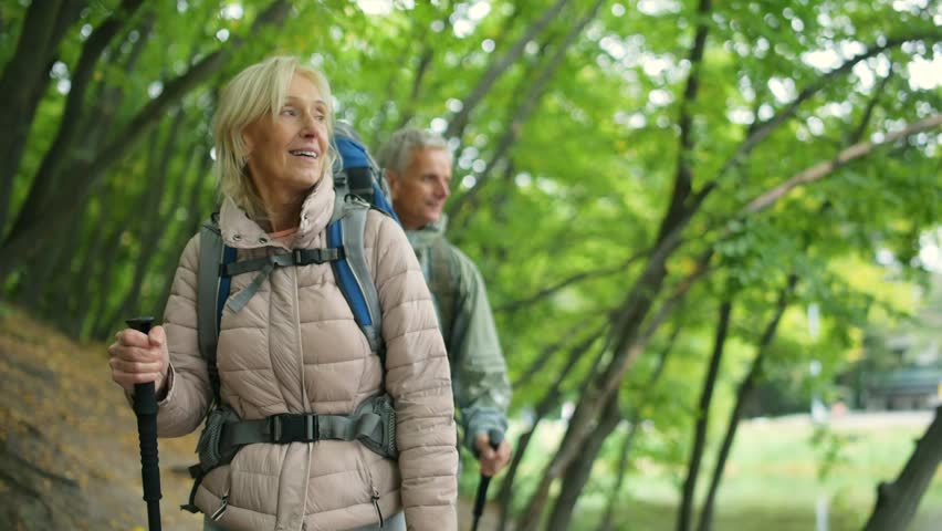 Positive retired woman walking with her husband in the wood | Shutterstock HD Video #31312408