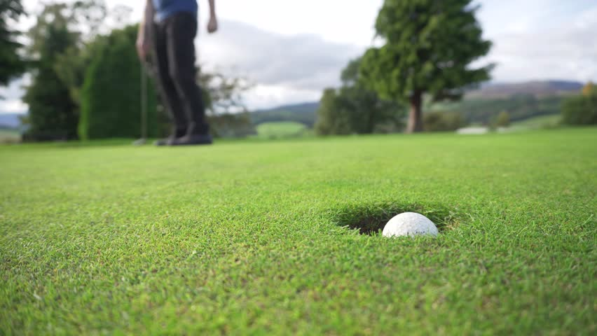 Golf Put by a Man on the Green, 4K Sports and Recreation. Course in Perthshire, Scotland, United Kingdom. Close up of Ball Sinking into the Hole.