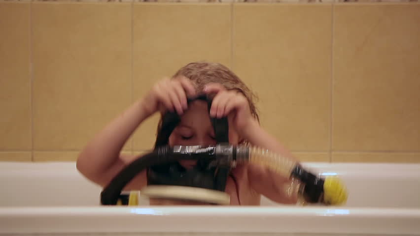 Small Caucasian girl in bath playing with mask and snorkel diving. Edited sequence.