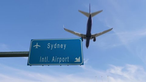 Sydney airport sign airplane passing overhead