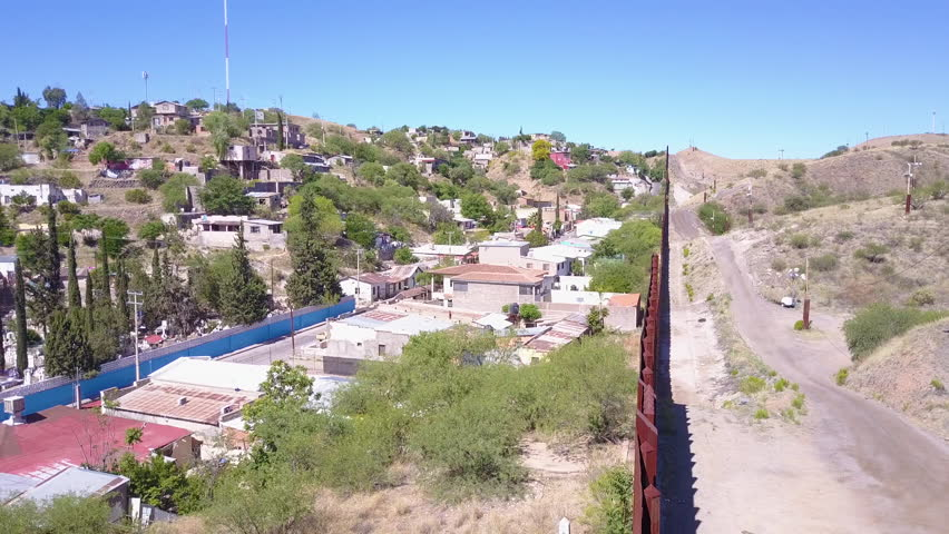 CIRCA 2010s - U.S.-Mexico border - Forward aerial along the U.S Mexican border wall fence reveals the town of Nogales. | Shutterstock HD Video #31373788