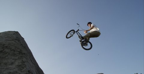 BMX athlete doing tricks on a jump in slow motion