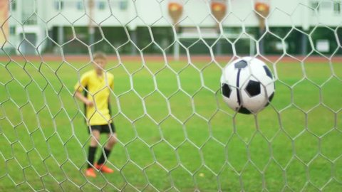 A young boy scores a goal during a penalty shoot out. Slow motion
