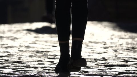 Silhouette and Shadow of Feet Walking on Cobblestones  - Amazing dark and light contrast shot showing a pair of legs walking on a cobblestone street in slow motion