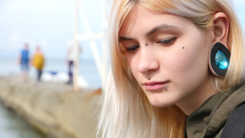 Bodimodification, portrait of a girl with face piercings and tunnels in the ears. a girl with a split tongue. shows the language. 4k, slow-motion shooting, copying space
