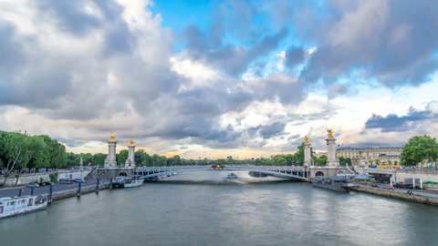 Bridge of Alexandre III spanning the river Seine timelapse hyperlapse. Decorated with ornate Art Nouveau lamps and sculptures. View from Invalides bridge. Paris. France. Blue cloudy sky before sunset