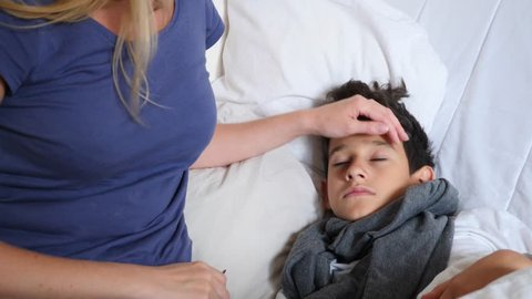 A sick baby boy was lying in bed with a fever, mama is caring for a sick son. 4k, slow-motion shooting, copy space