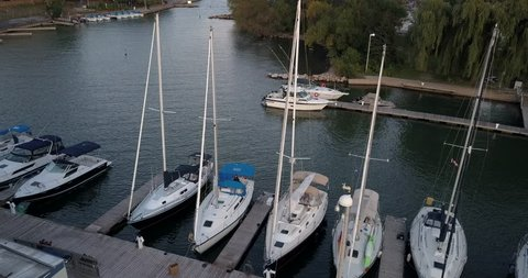 Drone hovers over a marina with sailboats gently rocking in the wind and small swell.  Sailors unfurl the foresail (genoa) for maintenance on one sailboat.