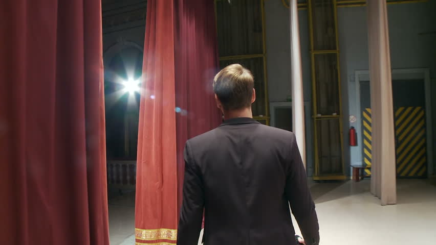 View from the back, the artist comes out behind the scenes onto the stage with a microphone and starts to sing