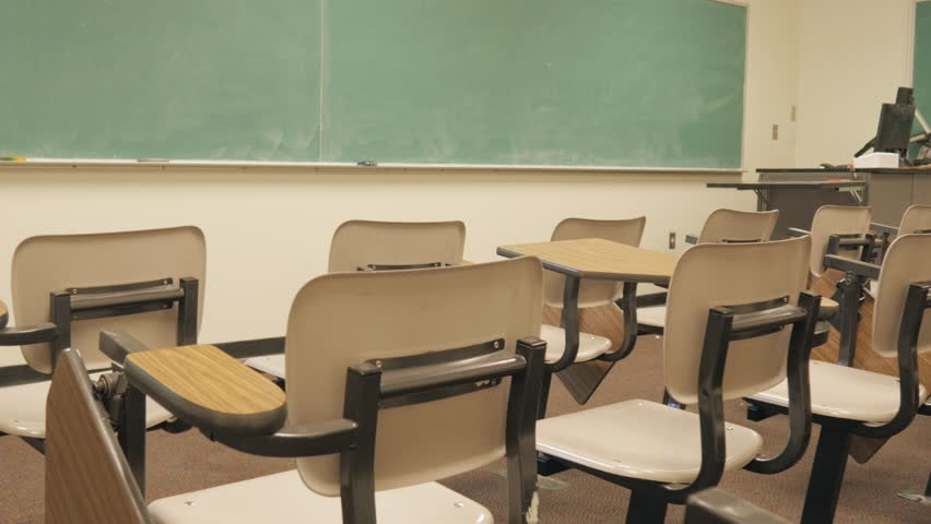 Push in towards blank chalkboard over empty school desks. The elementary school classroom has been abandoned. The campus has been evicted due to bullying, budget cuts, and lowered attendance rates.