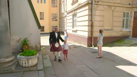 25 06 2016 Lviv Ukraine. Scottish man with his son. People wearing kilts, town street. The celtic heritage.
