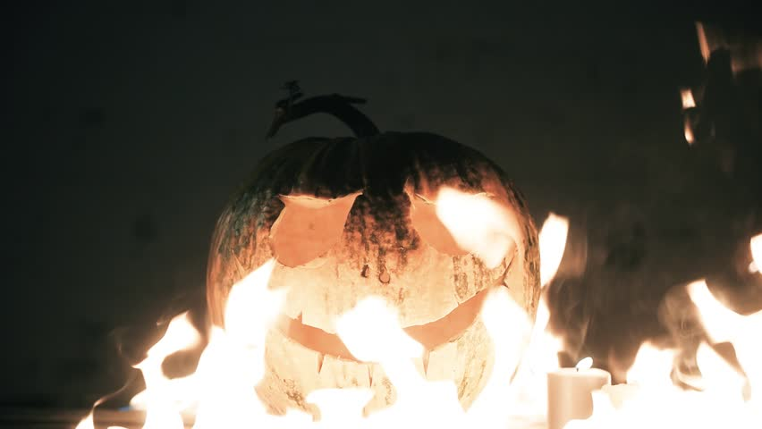 Scary carved halloween pumpkin. The big helloween pumpkin has a mad face with glowing eyes and also a glow in its mouth and teeth. Jack's lamp on fire. | Shutterstock HD Video #31469728
