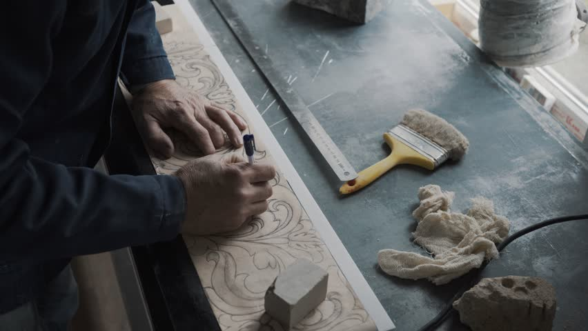 Worker traces lines with a stencil handle, the pattern is transferred to a marble slab using a carbon paper, a workplace, a sketch is drawn on lined paper