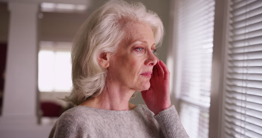 Close up of elder Caucasian woman with headache looking out window thinking. Close-up of unhappy older woman with migraine touching her temples. 4k