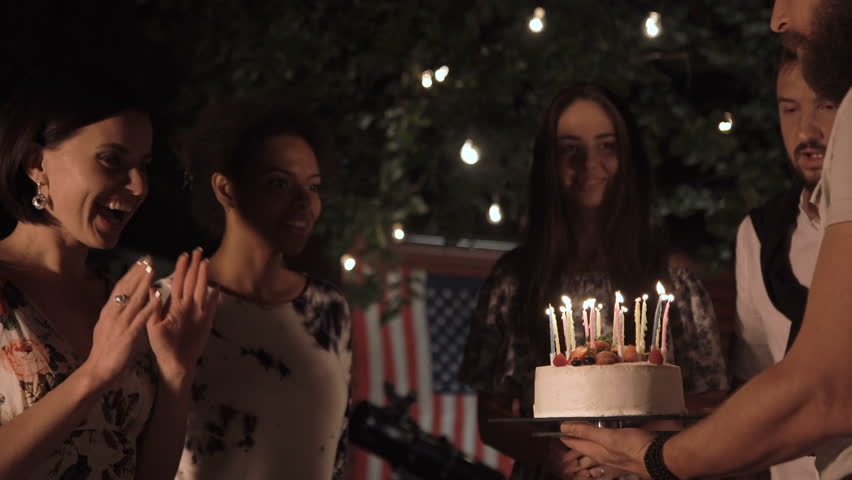Cheerful Men And Black Women Celebrating With Cake Candles On Backyard