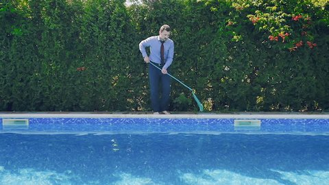 Businessman cleans the swimming pool with a nettle