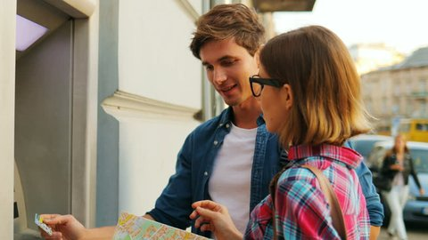 Cheerful couple looking happily at each other in front of the ATM machine while a young man is tryinh to withdraw money from ATM machine. Attractive caucasian woman is holding a city map. Outdoors.