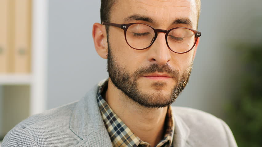 Close up face of an attractive caucasian man in spectacles, wearing a casual shirt and a grey shirt sitting at the office desk, looking and smiling at the camera.Indoor shot. | Shutterstock HD Video #31515658