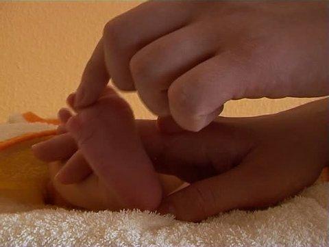 Mother tickling baby feet