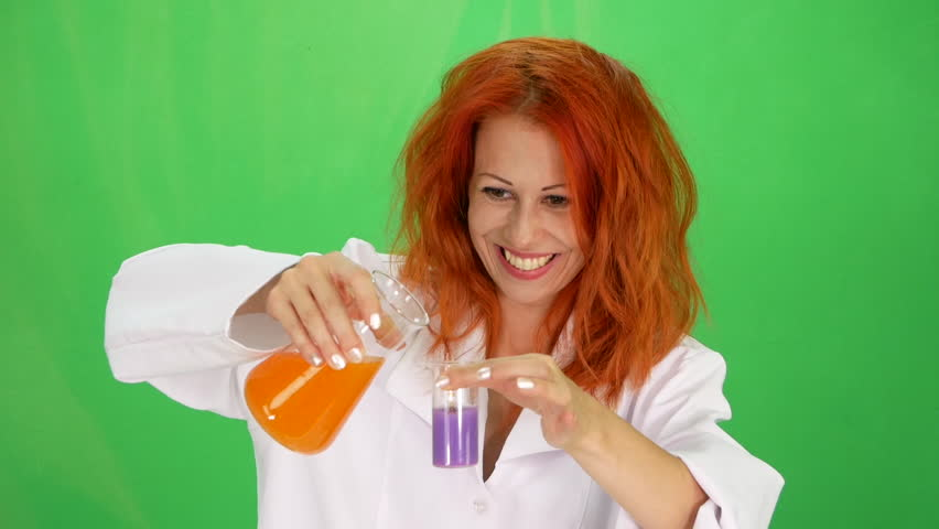 Beautiful funny young scientist mixes flasks with a purple and orange liquid at experiment   green-screen