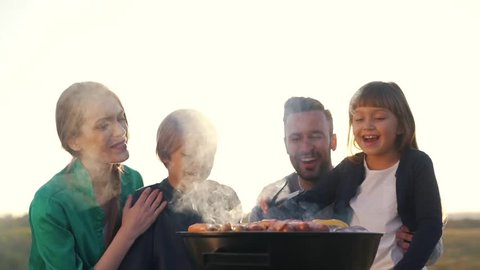 Happy family cook meat on grill.