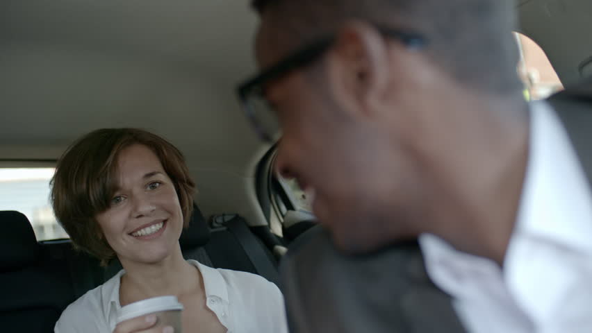 View from the inside of car of pretty businesswoman sitting on backseat with coffee cup, smiling and talking with corporate driver
