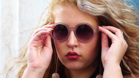 Young Stylish Woman Puts On Sunglasses