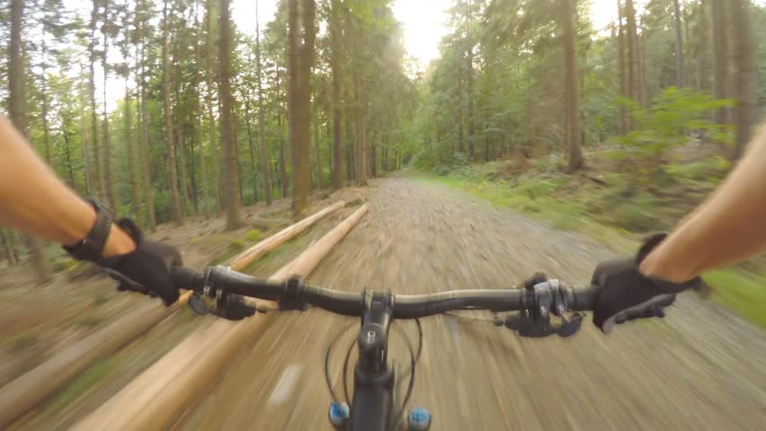 Mountain bike riding in green woods on double track long road. Forest extreme speed cycling, first person perspective view POV. Gimbal stabilized video GOPRO HERO4 4K.   Shutterstock HD Video #31581838