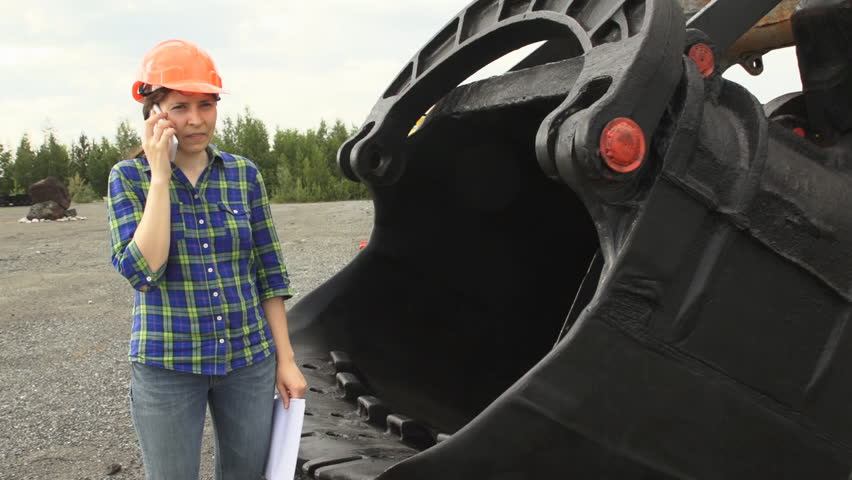 Portrait of a female worker in an orange helmet uses a white smartphone, stand next to a mining excavator.