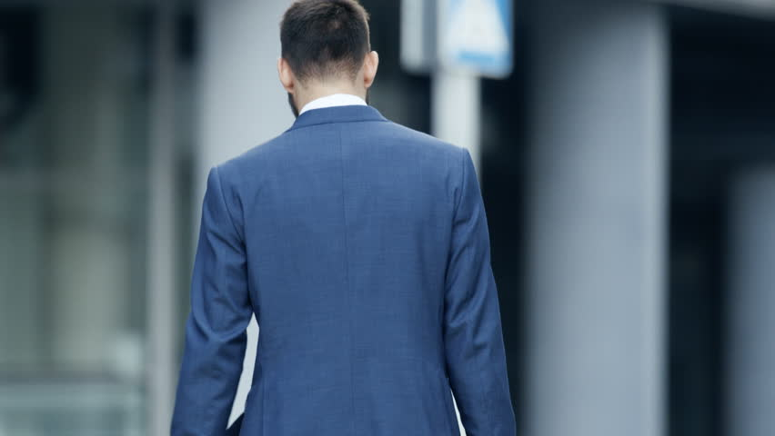 Back View of the Business Man in a Tailored Suit Walking on the Street of the Business District. Shot on RED EPIC-W 8K Helium Cinema Camera.