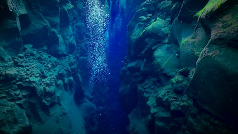 Bubbles rising up through deep blue underwater trench