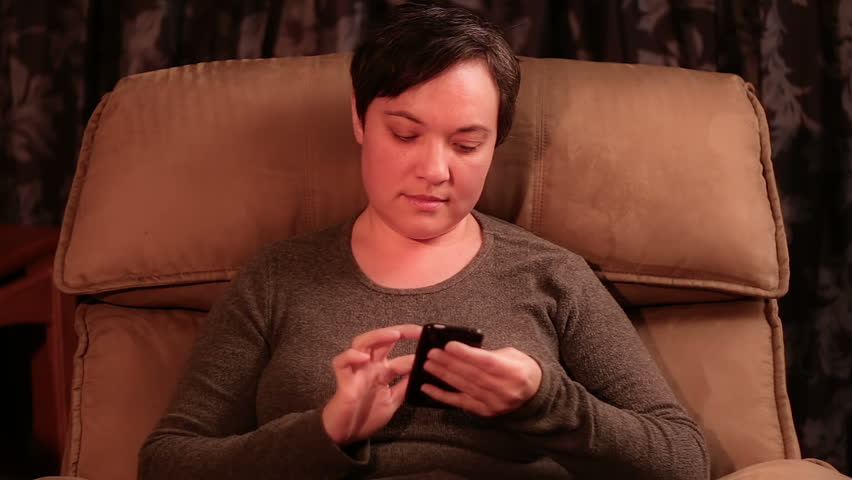 Woman texting while sitting in a recliner.