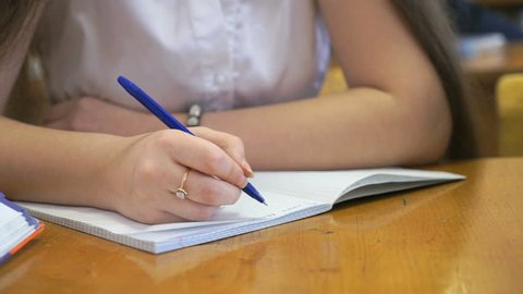 Schoolgirl dressed in a white chemise sits at a school desk writing text in exercise book using ballpoint pen. Close-up