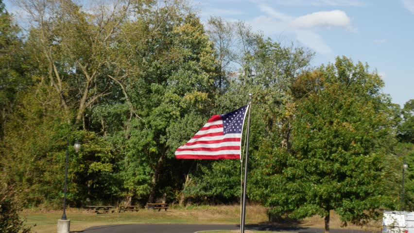 American Flag Blowing the Wind Trees in Background Super Slow Motion #31651684