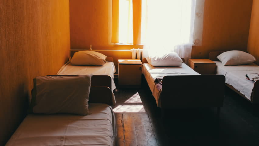 Many tucked beds in a children's camp or hospital
