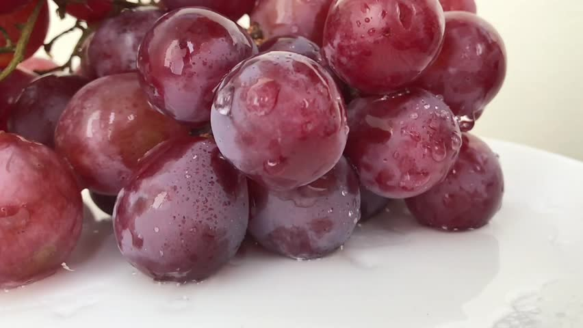 Slow motion: Fresh bunch black wine grapes with water drops rotate white background. A lot Red Grapes White background wet water droplet, authentic motion rain water droplets natural fruti lamp white