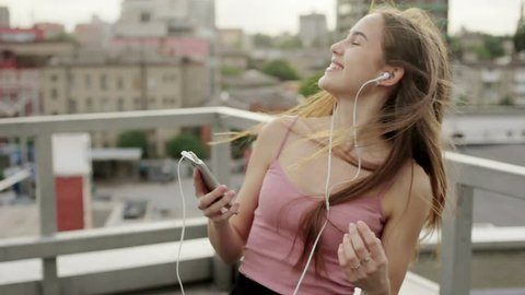 Music, technologies, VR, people, 4k and lifestyle concept - Girl listening music from smart phone mp3 player. at the sunny city streets and chatting with friends, sunset background