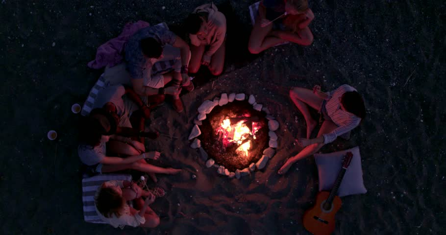 Birds eye view of friends with guitar at beach party roasting marshmallows above bonfire | Shutterstock HD Video #31710148