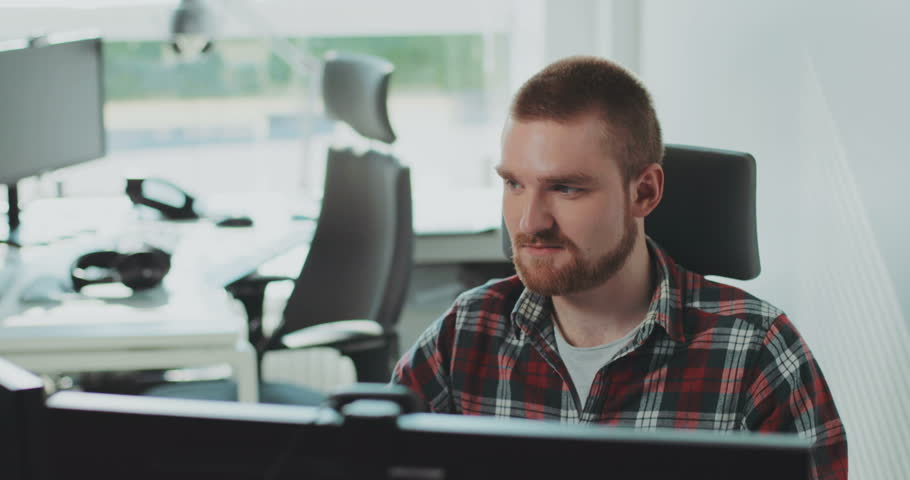 A young bearded man sits at a computer. Works in the office. Feels happy. Face, monitor, online, professional, table, workplace, architect. Contemporary design. Shot on RED Epic Camera. | Shutterstock HD Video #31727758