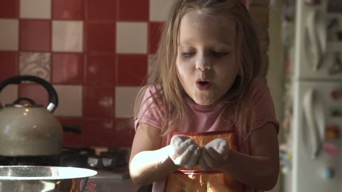 Adorable little girl blowing on flour while having fun and cooking on kitchen.