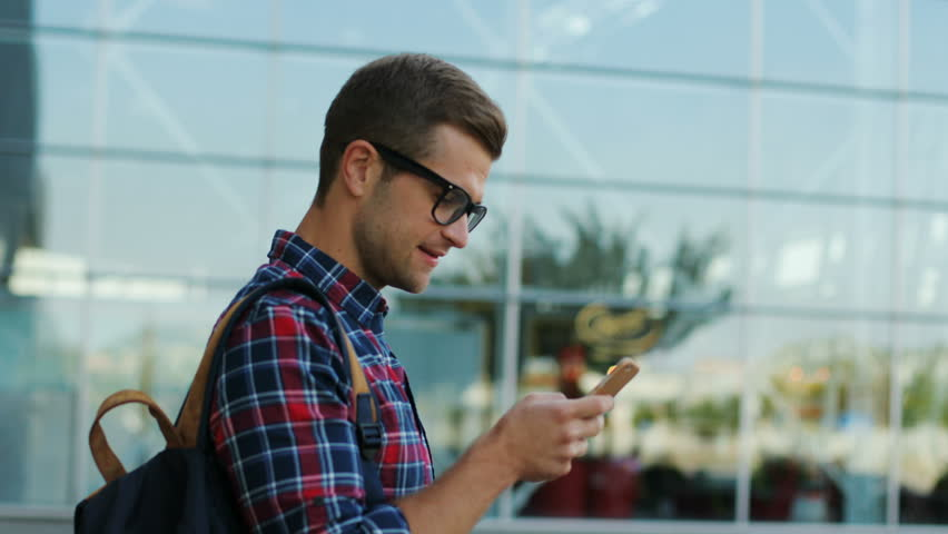 Close up. Portrait of a happy young man with a backpack. He surfs his phone. Then - looks around. Wearing glasses. Blurred background. | Shutterstock HD Video #31736308