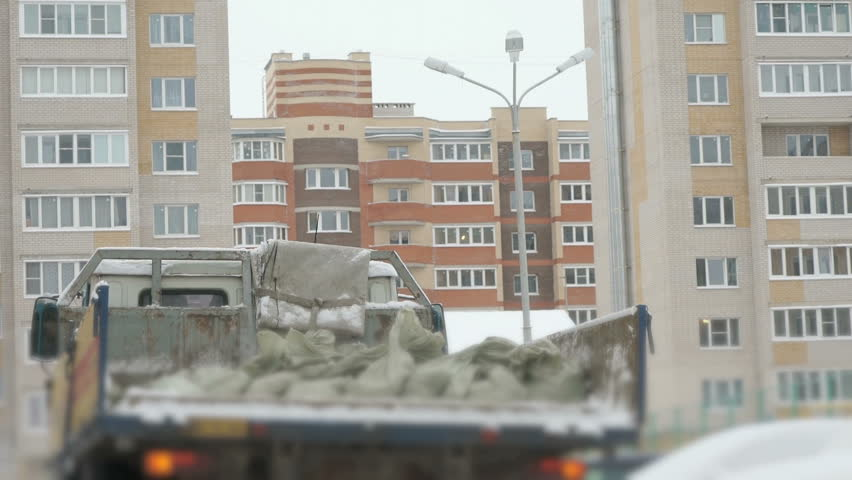 Truck takes out construction garbage in bags in the back in the winter, high-rise buildings #31737517