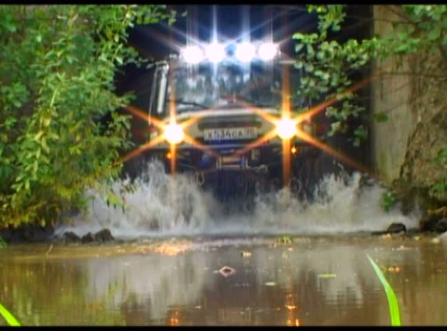 Off - road vehicle crossing the river in East Europe. Splashes of water from under weels. Slow motion