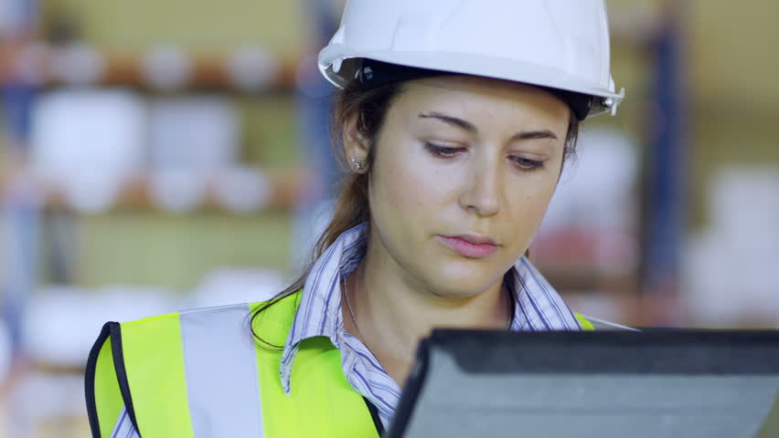 An attractive female warehouse employee wearing high visibility clothing and a hard hat is working on a digital tablet and checking her stock. In slow motion.