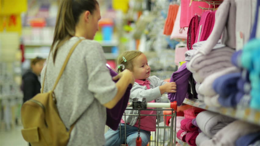 Closeup Portrait of Young Happy Family in Hypermarket. Cute Little Girl is Sitting in Supermarket Cart, Young Woman is Choosing Some Towel Standing near Market Shelf. | Shutterstock HD Video #31771507