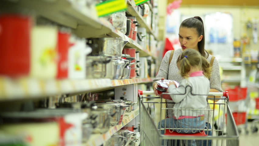 Portrait of Young Happy Family in Supermarket. Cute Little Girl is Sitting in Shopping Cart, Young Woman is Choosing Some Red Pan Standing near Market Shelf. | Shutterstock HD Video #31775368