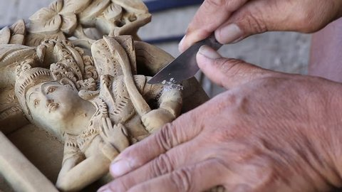 MANDALAY, MYANMAR - JANUARY 17, 2016 : Burmese man are making wooden souvenirs for tourists. Wood Carving is a traditional handicraft in Myanmar